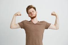 El retrato del hombre juguetón sano joven que muestra el bíceps muscles la jactancia mirando la cámara sobre el fondo blanco Fotos de archivo libres de regalías