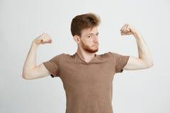 El retrato del hombre juguetón sano joven que muestra el bíceps muscles la jactancia mirando la cámara sobre el fondo blanco Imagenes de archivo