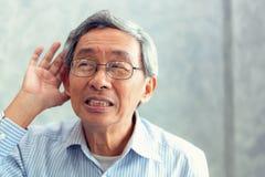 El retrato del hombre mayor a intentar oye algo sonar alrededor de él fotos de archivo