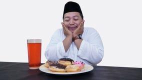 El retrato del hombre musulm?n gordo con el casquillo principal o el songkok ruega antes come y bebe para el ayuno de la rotura d fotografía de archivo libre de regalías