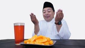 El retrato del hombre musulm?n gordo con el casquillo principal o el songkok ruega antes come y bebe para el ayuno de la rotura d fotos de archivo