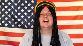 El retrato del hombre rastafarian feliz con teme en el fondo de una bandera de los E.E.U.U. metrajes