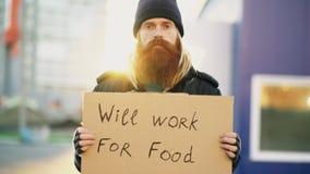 El retrato del hombre sin hogar joven con la cartulina que mira la cámara y quiere trabajar para la comida que mira la cámara la  imagenes de archivo