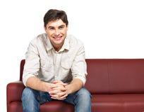 El retrato del hombre sonriente feliz joven se sienta en el diván fotos de archivo libres de regalías