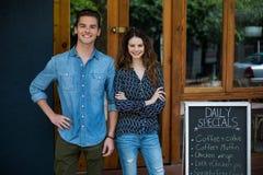 El retrato del hombre sonriente y la mujer que se coloca al lado del menú suben foto de archivo libre de regalías