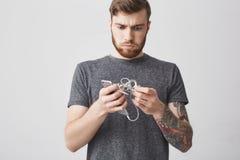 El retrato del hombre tatuado barbudo joven infeliz con el pelo oscuro en la tenencia de moda casual del equipo enredó los auricu Fotografía de archivo