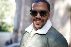 El retrato del inconformista afroamericano joven confiado feliz en desgaste formal y las gafas de sol que se sientan en la ciudad Imagenes de archivo