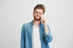El retrato del individuo hermoso joven con la barba discrepa hablando en el teléfono sobre el fondo blanco Fotografía de archivo