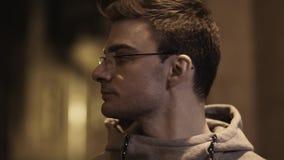 El retrato del individuo joven en vidrios fuera de la respiración da vuelta alrededor en backstreet metrajes