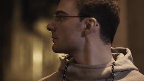 El retrato del individuo joven en vidrios fuera de la respiración da vuelta alrededor en pasillo metrajes