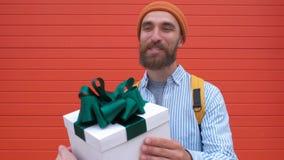 El retrato del júbilo barbudo emocionado del hombre para conseguir la caja de regalo blanca con el arco verde de hembra entrega l almacen de metraje de vídeo