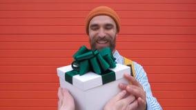 El retrato del júbilo barbudo emocionado del hombre para conseguir la caja de regalo blanca con el arco verde de hembra entrega l metrajes