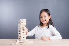 El retrato del juego de la muchacha bloquea el juego de madera en backgroun de madera de la tabla Fotografía de archivo
