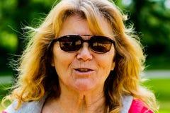 El retrato del más viejas mujeres envejeció 60 a 70 que está llevando las gafas de sol al aire libre más viejas mujeres hermosas  Foto de archivo