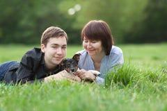 El retrato del mather feliz con el hijo y el perro Jack Russell en verano parquean Imagen de archivo libre de regalías