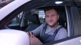 El retrato del mecánico de sexo masculino feliz que se sienta detrás de la rueda de un nuevo coche con una sonrisa mira la cámara metrajes
