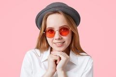 El retrato del modelo femenino encantado feliz en gafas de sol rojas redondas y sombrero elegante, guarda las manos debajo de la  Fotografía de archivo
