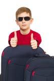 El retrato del muchacho con viaje empaqueta las gafas de sol que llevan que muestran los pulgares Imagenes de archivo