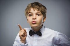 El retrato del muchacho enojado descontentado con amenaza al finger aislado en fondo gris Emoción humana negativa, facial Imagen de archivo libre de regalías