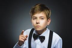 El retrato del muchacho enojado descontentado con amenaza al finger aislado en fondo gris primer Imágenes de archivo libres de regalías