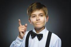 El retrato del muchacho enojado descontentado con amenaza al finger en fondo gris primer Imagen de archivo