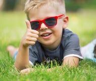 El retrato del muchacho feliz que muestra los pulgares sube gesto foto de archivo libre de regalías