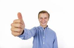 El retrato del muchacho fresco con la camisa azul que muestra los pulgares sube la muestra Imagen de archivo