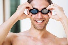 El retrato del nadador de sexo masculino sonriente joven adentro googlea Foto de archivo libre de regalías