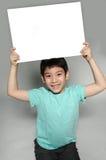 El retrato del niño asiático con la placa en blanco para añade su texto. Fotos de archivo