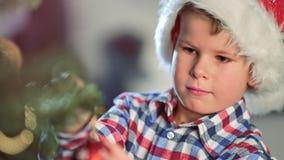 El retrato del niño pequeño enfocado adorna el árbol de navidad que sostiene el primer medio de la bola de los ornamentos almacen de metraje de vídeo