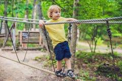 El retrato del niño pequeño lindo camina en un puente de cuerda en un adventu Foto de archivo libre de regalías