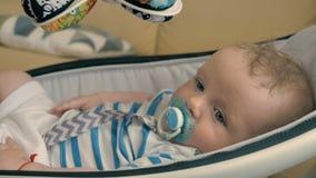 El retrato del niño pequeño lindo con el maniquí está oscilando por la cuna moderna metrajes