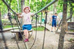 El retrato del niño pequeño lindo y la muchacha caminan en un puente de cuerda en un parque de la cuerda de la aventura Fotos de archivo
