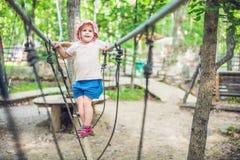 El retrato del niño pequeño lindo y la muchacha caminan en un puente de cuerda en un parque de la cuerda de la aventura Fotografía de archivo