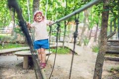 El retrato del niño pequeño lindo y la muchacha caminan en un puente de cuerda en un parque de la cuerda de la aventura Imagenes de archivo