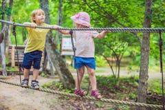 El retrato del niño pequeño lindo y la muchacha caminan en un puente de cuerda en un parque de la cuerda de la aventura Imágenes de archivo libres de regalías