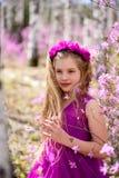El retrato del niño se coloca entre el ledum y el abedul en un vestido y una sonrisa rosados Foto de archivo