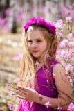 El retrato del niño se coloca entre el ledum y el abedul en un vestido y una sonrisa rosados Foto de archivo libre de regalías