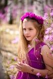 El retrato del niño se coloca entre el ledum y el abedul en un vestido y una sonrisa rosados Fotografía de archivo libre de regalías