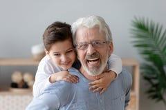 El retrato del nieto feliz tiene el abuelo a cuestas sonriente de la diversi?n fotos de archivo libres de regalías