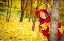 El retrato del otoño de la mujer hermosa sobre amarillo se va mientras que camina en el parque en caída Emociones y concepto posi fotografía de archivo