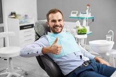 El retrato del paciente feliz en la silla dental, demostraciones gesticula la clase imagen de archivo libre de regalías