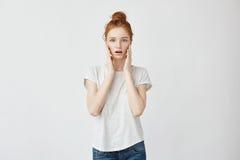 El retrato del pelirrojo sorprendió a la muchacha con las manos en mejillas Fondo blanco, espacio de la copia Fotos de archivo