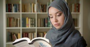 El retrato del perfil del estudiante musulm?n en libro de lectura del hijab atento sonr?e en c?mara en la biblioteca almacen de metraje de vídeo