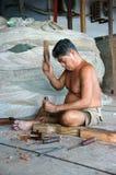 El retrato del pescador pela la madera en la tienda de la red de pesca en marco vertical. CA MAU, VIETNAM 29 DE JUNIO Imagen de archivo libre de regalías