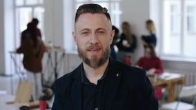 El retrato del primer del centro barbudo feliz envejeció al jefe masculino de la compañía en traje negro que sonreía en la cámara almacen de video
