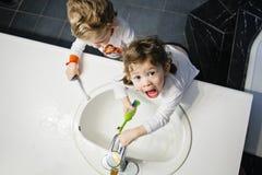 El retrato del primer de gemelos embroma a la muchacha del niño pequeño en las manos de la cara del retrete del cuarto de baño qu Fotografía de archivo libre de regalías