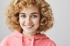 El retrato del primer de la muchacha caucásica femenina linda con free peinado que sonríe ampliamente mientras que se opone a gri Fotos de archivo libres de regalías