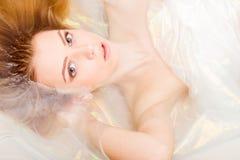 El retrato del primer de la muchacha hermosa de la mujer rubia joven encantadora está en el agua brillante que mira la cámara fotografía de archivo