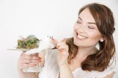 El retrato del primer de la muchacha hermosa emocional toca un pájaro y una sonrisa En un fondo blanco Foto de archivo libre de regalías